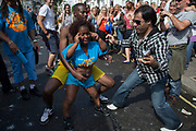 People joking and laughing and dancing along with a woman dwarf at the Notting Hill Carnival in West London. The Notting Hill Carnival is an annual event which since 1964 has taken place each August, over two days (the August bank holiday Monday and the day beforehand). It is led by members of the West Indian / Caribbrean community, particularly the Trinidadian and Tobagonian British population, many of whom have lived in the area since the 1950s. The carnival has attracted up to 2 million people in the past, making it the second largest street festival in the world. The celebration centres around a parade of floats, dancers and sound systems.