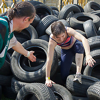 Competitors run through a tyre obstacle during the Brutal Run extreme obstacle course race in Budapest, Hungary on August 30, 2014. ATTILA VOLGYI