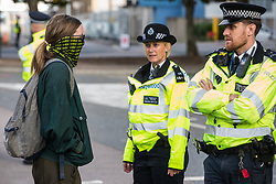 London, UK. 5 September, 2019. A masked activist speaks to Metropolitan Police officers during protests outside ExCel London on the fourth day of a week-long carnival of resistance against DSEI, the world's largest arms fair.