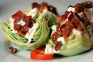 Andrew Blair's The Montford Wedge is a wedge of crisp iceberg topped with creamy Gorgonzola blue cheese dressing, caramelized pecans, crispy bacon and chopped red and yellow tomatoes.
