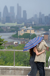 ©Licensed to London News Pictures 02/07/2020     <br /> Greenwich, UK. A couple kissing under an umbrella. People out and about in Greenwich Park, Greenwich, London today as the Coronavirus lockdown is eased. The weather continues to be unsettled with heavy rain and sunshine. Photo credit: Grant Falvey/LNP