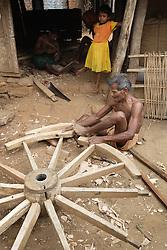 A skilled wheelwright repairing the wooden wheels of a buffalo cart. Madhusmita Moharana, (Carpanter), Male, 65, behind him his grand-daughter Laxmi Behera, 5 years (Yellow frock). Ratapata Village, Badamba, INDIA