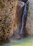 A small cascade and seeping spring with rainbow in afternoon light. Aravaipa Canyon wilderness