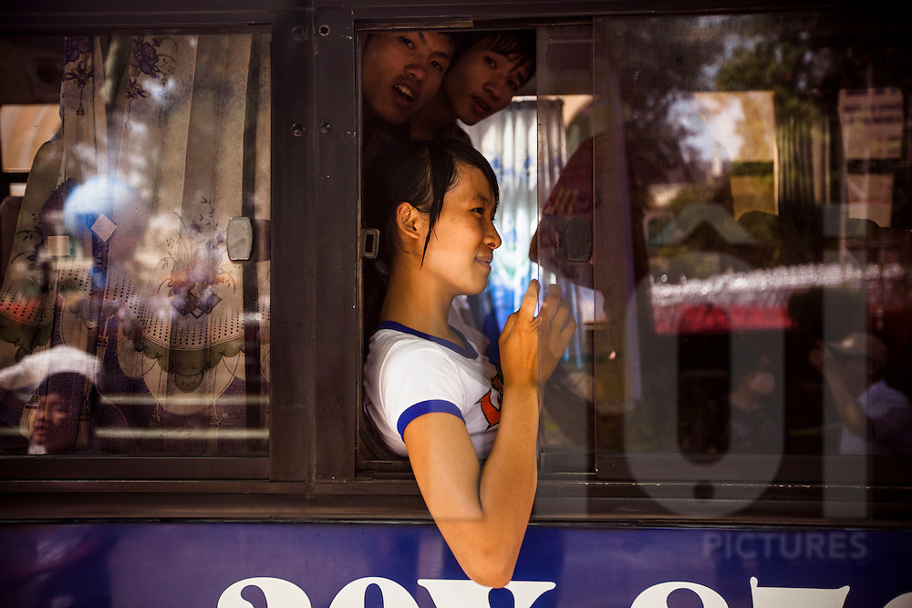 A young Vietnamese girl leans her elbow out a bus window as two teenagers peer out over her head, Hanoi, Vietnam, Southeast Asia