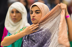 A woman prepares for prayers during the Eid in Excel event, in association with the Al-Khair Foundation, at ExCeL London, which is London's largest Eid celebration.