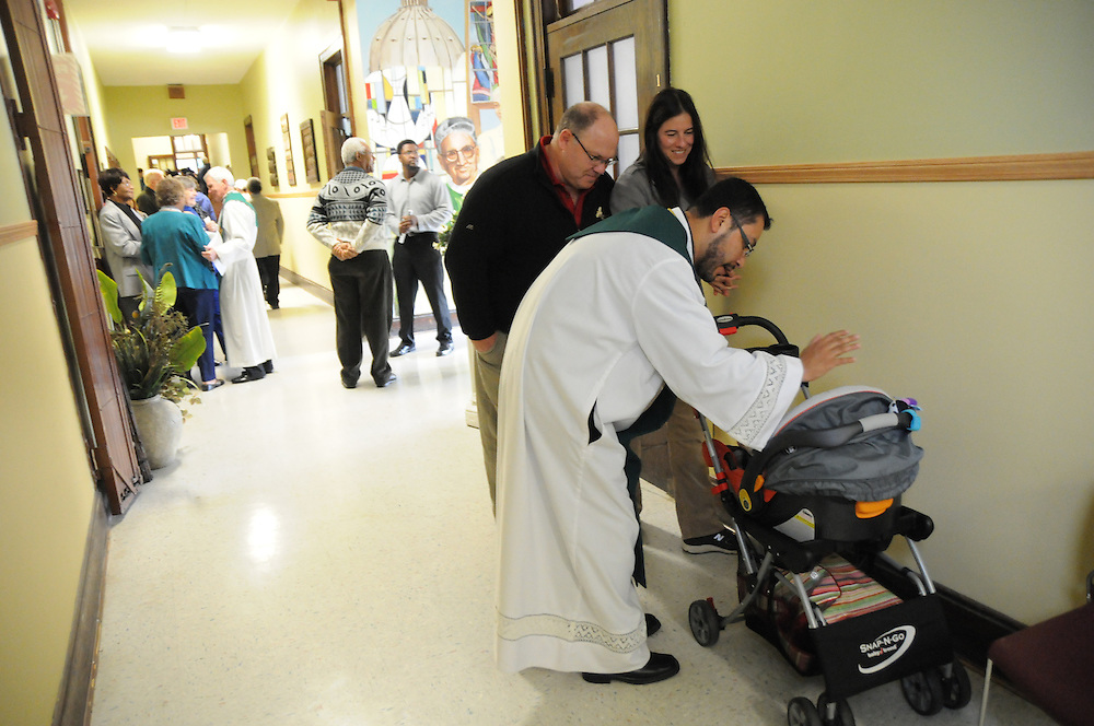 Pastor Carmelo Mendez blesses one month-old Robert Politi, who was recently adopted by parents Paul and Anne Politi (center), in the hallway of the newly-inaugurated Quinn Community Center. The entryway mural designed by Anne(background) features an image of the building's namesake, former St. Eulalia Pastor William Quinn. Quinn made a lasting history for himself as a pioneer for social justice, both in the fields of civil rights, along with those of immigrants in the U.S. He died in 2004.
