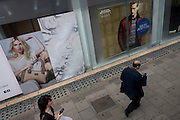 Two smartphone consumers walk along a London street next to fashion ad posters.