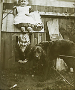 Boy and girl brother and sister playing with dog kennel in garden C 1900-1910 ,England, UK
