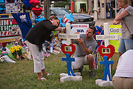 Woman writes a message on a cross at a makeshift memorial where six officers were shot on Airline Highway in Baton Rouge. Three of the officers were killed and another one remains in critical condition. The memorial in from of the  B-Quik gas station  continues to grow.