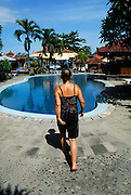 Austrailan tourist woman walking toward hotel swimming pool. Sanur, Bali, Indonesia