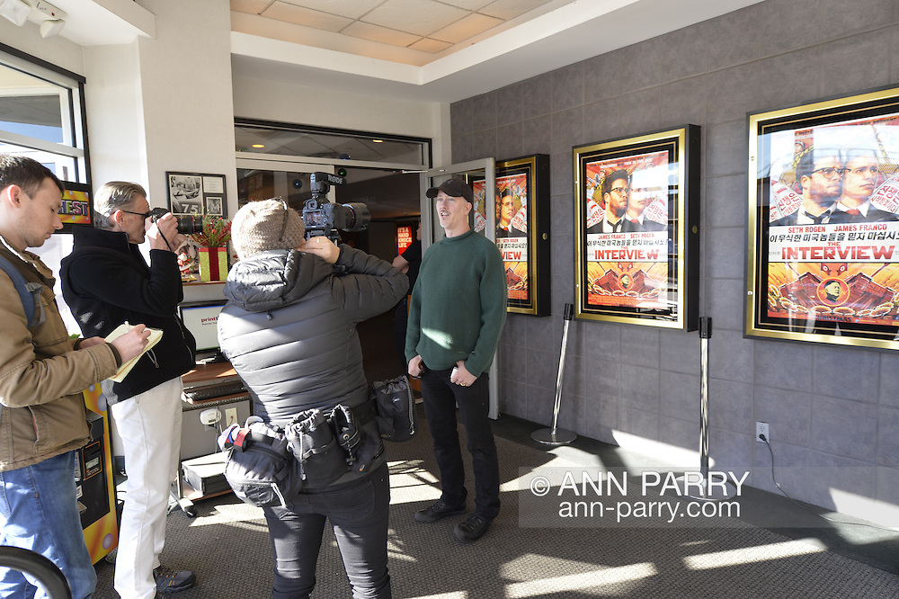 Merrick, New York, USA. December 25, 2014. A movie patron is interviewed by a Newsday reporter where The Interview, the controversial comedy by Sony Pictures Entertainment, plays at Merrick Cinemas, thought to be the only movie theater showing it in Nassau County, Long Island, on Christmas Day. In November, hackers hacked Sony Pictures computers, and later threatened theaters planning to show The Interview, in which stars James Franco and Seth Rogen play civilians recruited by CIA to assassinate North Korea dictator Kim Jong-un. Due to the terrorist threats, Sony originally canceled public release of the film, but then changed its plans again, and released the film in a limited way, including several hundred independent theaters, against the attempt to suppress the American First Amendment Right to Free Speech.