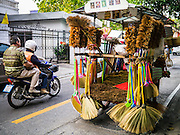 """05 MARCH 2013 - BANGKOK, THAILAND:  A broom vendor pushes his cart past a motorcycle taxi in an upscale neighborhood in Bangkok. Thailand's economic expansion since the 1970 has dramatically reduced both the amount of poverty and the severity of poverty in Thailand. At the same time, the gap between the very rich in Thailand and the very poor has grown so that income disparity is greater now than it was in 1970. Thailand scores .42 on the """"Ginni Index"""" which measures income disparity on a scale of 0 (perfect income equality) to 1 (absolute inequality in which one person owns everything). Sweden has the best Ginni score (.23), Thailand's score is slightly better than the US score of .45.  PHOTO BY JACK KURTZ"""
