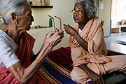 Vengalashmi and Dhanalashmi talk in their room, Tamaraikulum Elders village, Tamil Nadu, India