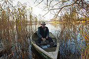 A German fisherman in his boat, in Uckermarkische Seen Natural park, part of the The Feldberg Lake District Nature Park containing large lakes, kettle bogs, and an abundance of plant and animcal species. Brandenburg, Germany.