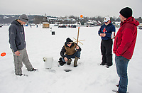 Adam McCarthy, Jon King, Bob King and Keith McCarthy set up tipups around their bob house on Meredith Bay Village Saturday morning.  The King's have been fishing in the derby for 26 years. (Karen Bobotas/for the Laconia Daily Sun)
