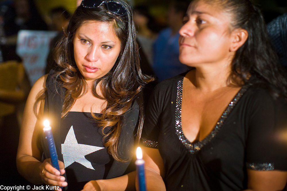 11 OCTOBER 2010 - PHOENIX, AZ:  LIZ MONTALVO (left) and GEORGINA SANCHEZ, participate in a candle light vigil in front of Phoenix police headquarters Monday. About 300 people gathered at the Phoenix Police Department headquarters building Monday night to protest the shooting of Daniel Rodriguez and his dog. The officers responded to a 911 call made by Rodriguez' mother. A scuffle ensued when they arrived and Phoenix police officer Richard Chrisman shot Rodriguez, who was unarmed, and his dog. Chrisman then allegedly filed a false report about the event. He has been arrested on felony assault charges. The event has angered some in the Latino community and they have held a series of protests at the police headquarters. They want Chrisman charged with murder.    Photo by Jack Kurtz