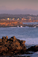 Coastal fog at sunset over quaint small town village atop rocky bluffs over the Pacific Ocean, Cambria, California