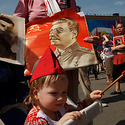 A child drinks milk during a Communist march in central Moscow on Victory Day with portraits of Soviet dictator Josef Stalin.