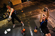 Kaycie Brelo, 30, left, and Neel Goel, 28, swing and lift kettle bells at the Psycho Gym in Dallas, Texas, on December 20, 2012.  (Stan Olszewski/The Dallas Morning News)