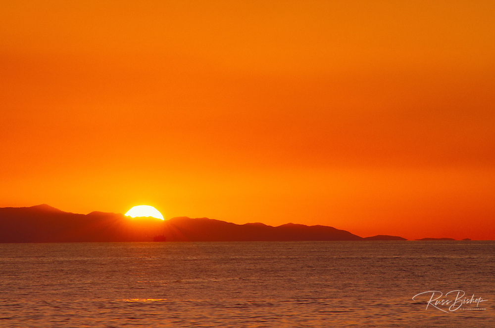Sun setting behind Santa Cruz Island (off shore oil platform visible), Channel Islands National Park, California USA