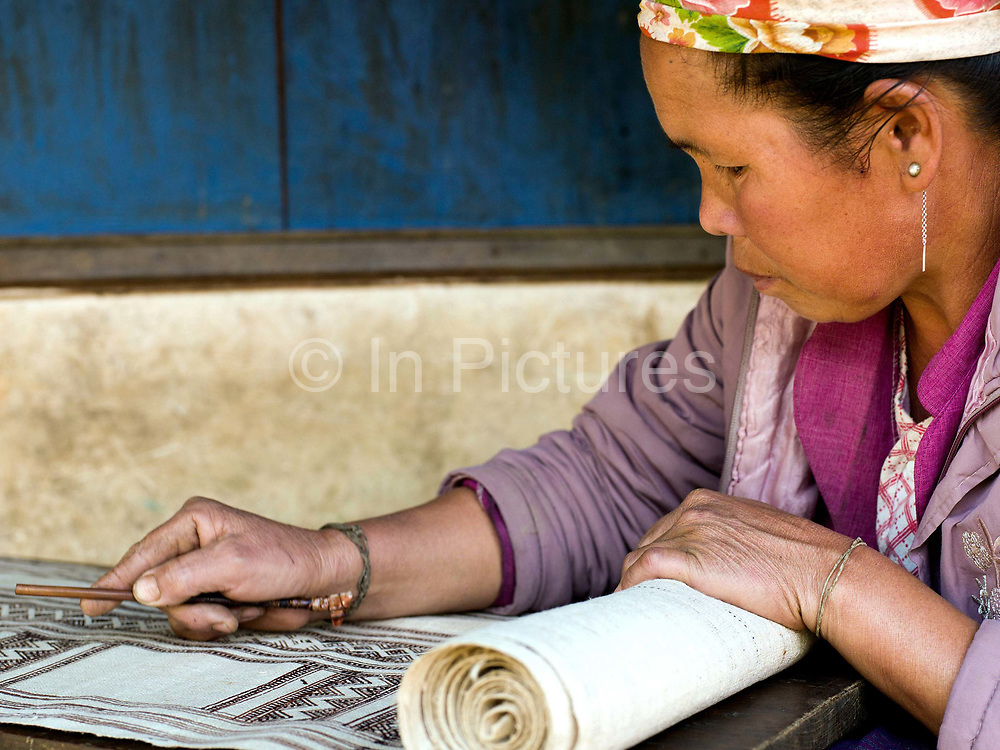 Nan Ya, a Hmong Leng ethnic minority woman decorates the woven hemp fabric by batik, a wax resist technique in Thien Pha, Houaphan province, Lao PDR. Bees' wax is collected from the forest, heated in small metal pots and mixed with indigo paste (which colours the wax and makes it easier to see on the cloth). A bamboo pen with a metal nib is used for drawing the wax onto the hemp. The wax marks will resist the dye when the cloth is dipped in the indigo dye bath and left to dry. After the last dye bath has been completed, the cloth is boiled to remove the wax. The resulting fabric is an indigo blue colour with white designs. Making hemp fabric is a long and laborious process which the Hmong women make into skirts for their traditional clothing. In Lao PDR, hemp is now only cultivated in remote mountainous areas of the north.