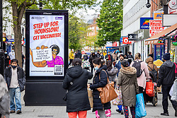 Licensed to London News Pictures. 25/05/2021. London, UK. Shoppers walk past a Covid-19 information sign in Hounslow west London as Downing Street issues a non-essential travel ban to areas in England affected by the Indian variant including Hounslow in London. On Sunday the government increased surge testing in the area to help combat the new variant. Photo credit: Alex Lentati/LNP