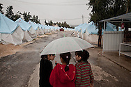 Iman Kasif, centre, walks with her friends through the rainy Yayladagi refugee camp for Syrians in southern Turkey. 12/21/2012 Bradley Secker for the Washington Post