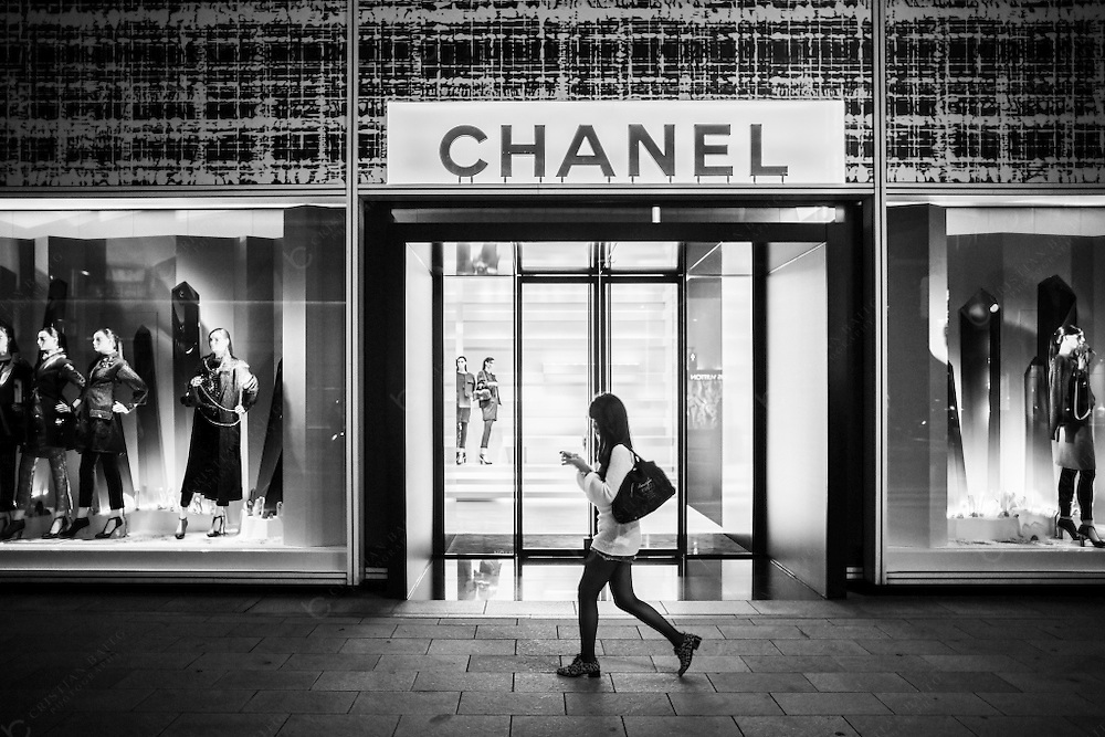 Women walking in front of Chanel luxury store in Ginza Tokyo Japan. This luxury brand founded in 1909 by Coco Chanel specializes in high couture to parfums and other luxury goods.With over 300 shops worldwide this shop in Ginza is the flagship store in Japan.