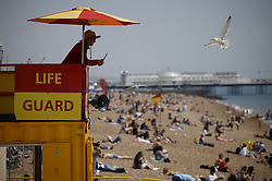 © Licensed to London News Pictures. 24/06/2021. Brighton, UK. A life guard keeps an eye out as visitors to Brighton enjoy the warm weather on the beach. After recent rain, a period of high temperatures and sunshine is forecast in the south. Photo credit: Peter Macdiarmid/LNP