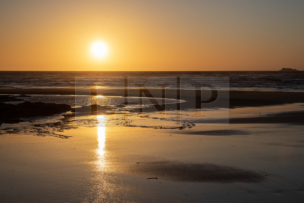 © Licensed to London News Pictures. 02/04/2020. Padstow, UK. The sun sets over Constantine Bay on the north coast of Cornwall after a warm clear day. Warm weather is expected next week. Photo credit : Tom Nicholson/LNP