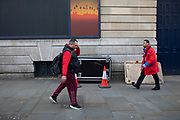 Passers by interact with a poster of an idillic sunset in red and orange depicting a silhouette of palm trees on 18th February 2020 in London, England, United Kingdom. While people walk by on a grey winter day, the poster offers a small window into another World where paradise can be found.