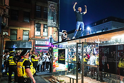 © Licensed to London News Pictures . 07/07/2021. Manchester, UK. Police intervene to remove people from the rooves of bus shelters as hundreds of fans and revellers pack in to Stevenson Square in Manchester City Centre as celebrations take place following Englands victory over Denmark in the European Cup secured the team a place in the cup final . Photo credit: Joel Goodman/LNP