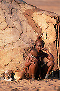 Himba woman & child beside trad- itional house. Kaokoland Namibia