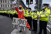 Protester with a placard reading 'Oil money is blood money' as Metropolitan police wearing face masks form a cordon at Extinction Rebellion demonstration on 3rd September 2020 in London, United Kingdom. With government resitting after summer recess, the climate action group has organised two weeks of events, protest and disruption across the capital. Extinction Rebellion is a climate change group started in 2018 and has gained a huge following of people committed to peaceful protests. These protests are highlighting that the government is not doing enough to avoid catastrophic climate change and to demand the government take radical action to save the planet.