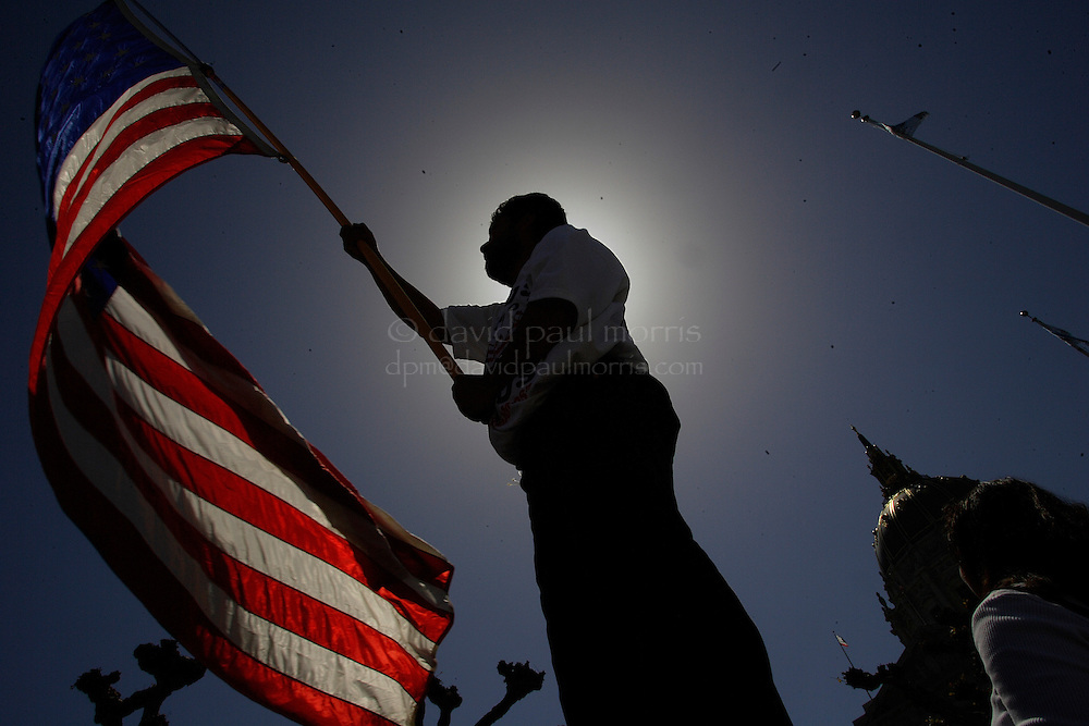 """SAN FRANCISCO- MAY 1:  A man holds an American flag in front of city hall as the joins over 30,000 people who marched down Market Street as they take part in """"A Day Without Immigrants""""  on May 1, 2006 in San Francisco, California. They were joined by over a million people nationwide as they try to prod Congress to allow the nation's more then 11 million illegal immigrants a chance to become citizens. Photo by David Paul Morris"""