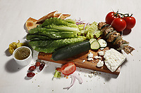 Salad ingredients - lettuce, cucumber, tomato, chicken kababs, feta cheese, dates, onion