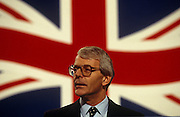 British Prime Minster John Major addresses his Conservative Party conference in Brighton. Behind him is large image of a Union Jack flag that seemingly flutters patriotically in the background, as if giving him the appearance of a man of the people. Major was PM from 1990-97 after Margaret Thatcher loss of popularity and subsequent removal from office. Here, Major delivers a speech in front of the flag at the annual get-together of party faithful in 1994.