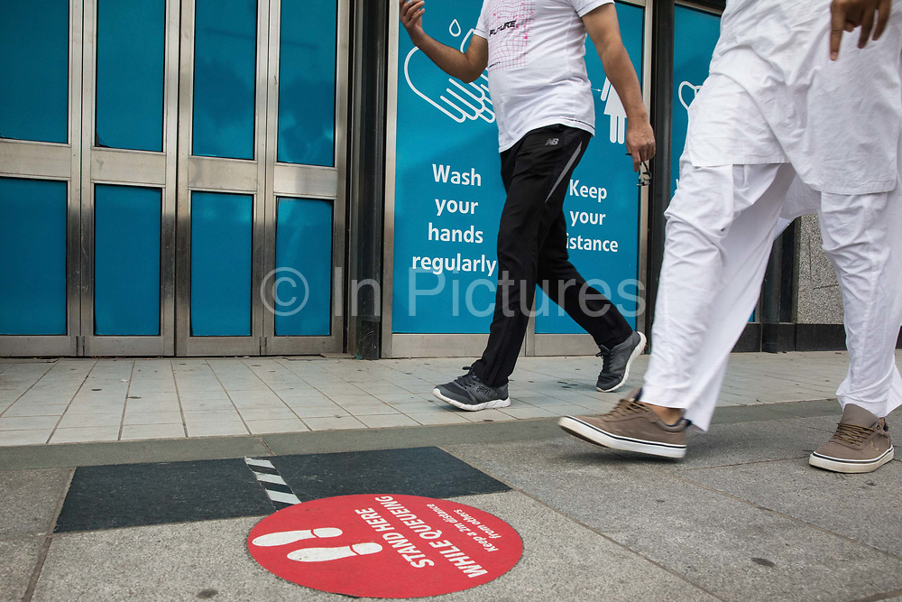 Members of the public walk past COVID-19 post lockdown public information displays on 21st August 2020 in Slough, United Kingdom. Slough has been listed by Public Health England PHE and the Department for Health and Social Care DHSC as an 'area of concern' for COVID-19 following a rise in positive coronavirus cases over the last two weeks.