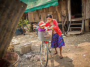 """28 FEBRUARY 2014 - MAE SOT, TAK, THAILAND: A Burmese woman and her child leave their home to go shopping in Mae Sot. Mae Sot, on the Thai-Myanmer (Burma) border, has a very large population of Burmese migrants. Some are refugees who left Myanmar to escape civil unrest and political persecution, others are """"economic refugees"""" who came to Thailand looking for work and better opportunities.    PHOTO BY JACK KURTZ"""