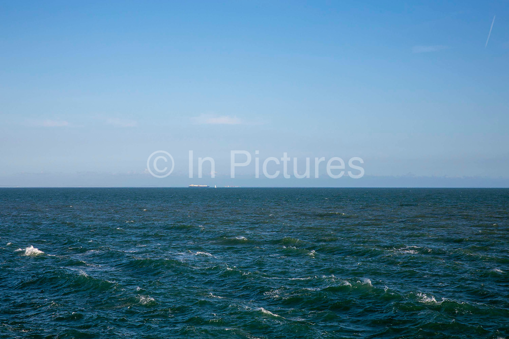 Ships sit on the horizon in the English Channel from Folkestone, Kent, England, United Kingdom.