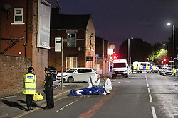 © Licensed to London News Pictures. 26/07/2020. Manchester, UK. Forensic scenes of crime examiners working on Henbury Street. A 17 year old boy has been stabbed to death and three others stabbed causing injuries , in the Moss Side area of South Manchester this evening. Photo credit: Joel Goodman/LNP