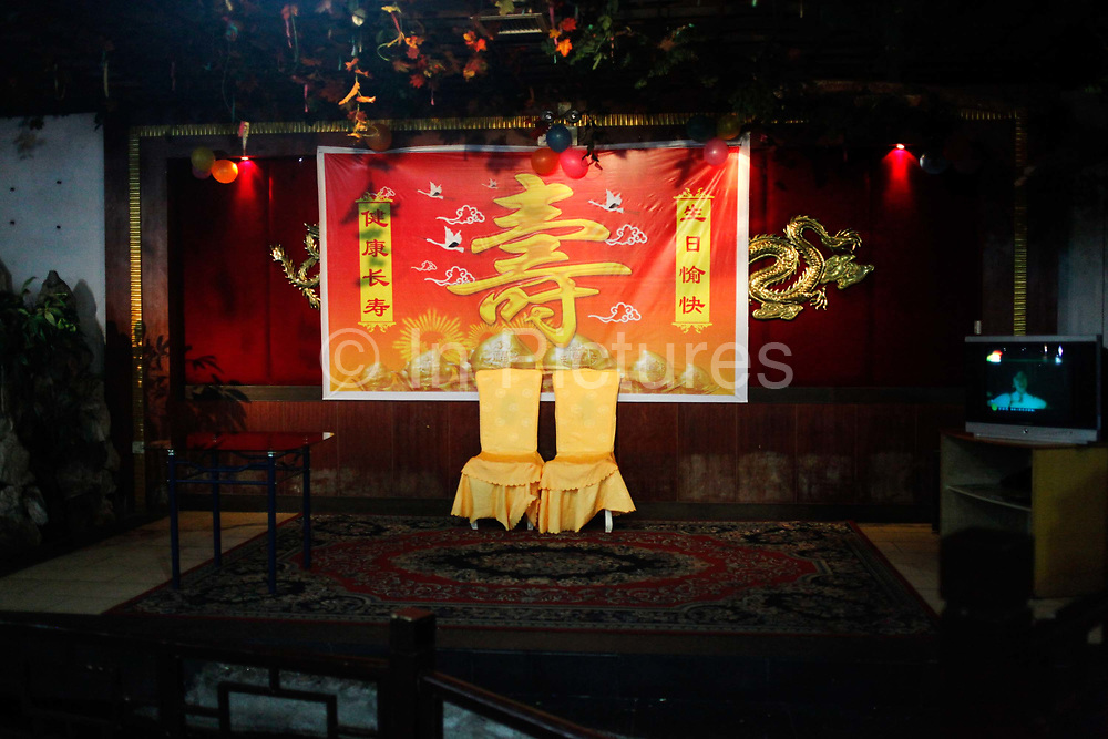 """Chairs and adornments sits in a hotel restaurant after a birthday party in Daoxian, Hunan Province, China, on Saturday, 16 October 2010.  The large character on the backdrop is """"shou"""", which means longevity."""