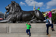 Young tourists climb on top of one of four lions at the base of Nelson's Column in Trafalgar Square, on 10th August 2017, in London, England.