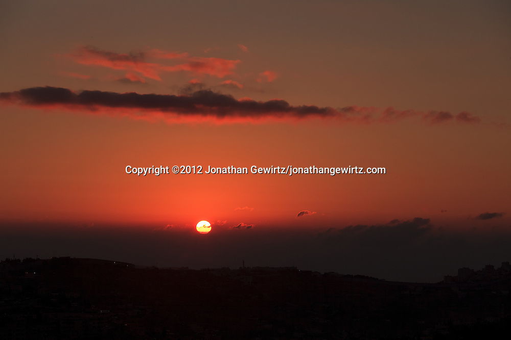 The sun rises over the Mountains of Moab in the distance behind the village of Abu Dis on the eastern outskirts of Jerusalem. WATERMARKS WILL NOT APPEAR ON PRINTS OR LICENSED IMAGES.
