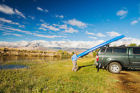 A kayaker unloads his boat and gets ready to paddle Owens River at the base of The Eastern Sierra Mountains, California.