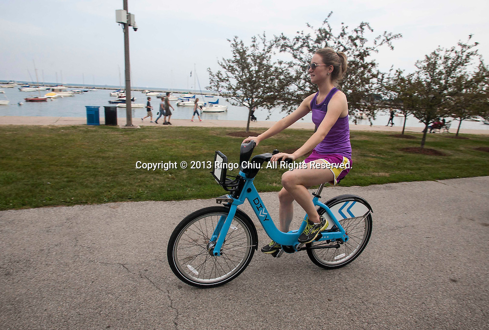 A woman rides a Bivvy bike along the lakefront on Monday, August. 19, 2013 in Chicago, Illinois. Divvy is a bicycle sharing system that launched in Chicago on June 28, 2013 with 750 bikes at 75 stations spanning from the Loop north to Fullerton Ave, west to Damen Ave, and south to 23rd St. The system is planned to grow to 3000 bikes at 300 stations by August 2013 and 4,000 bicycles at 400 stations by Spring 2014.(Photo by Ringo Chiu/PHOTOFORMULA.com)