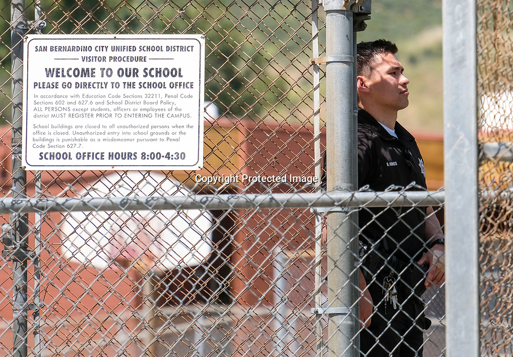 Police officers stands guard at North Park School after a shooting ,Monday, April 10, 2017, in San Bernardino, Calif.. An apparent murder-suicide inside an elementary school classroom in San Bernardino left two adults dead, including a teacher, and two students wounded, police and school officials said. (AP Photo/Ringo H.W. Chiu)