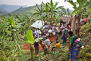 Locals from the community gather with others from the Batwa tribe and the family for the funeral of Matale, a local woman who died of cancer. Her coffin is carried to the hole dug in the family garden where it is buried.