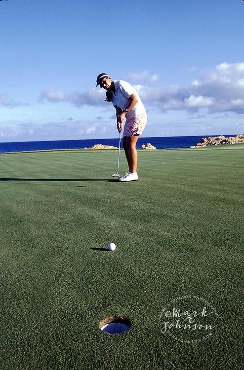 Mexico, Baja California, Cabo San Lucas, woman golfer on seaside green ****Model Release available