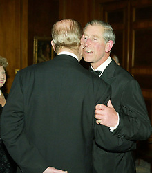 The Prince Of Wales greets the Duke of Edinburgh during a return banquet at the Italian Ambassador's residence.